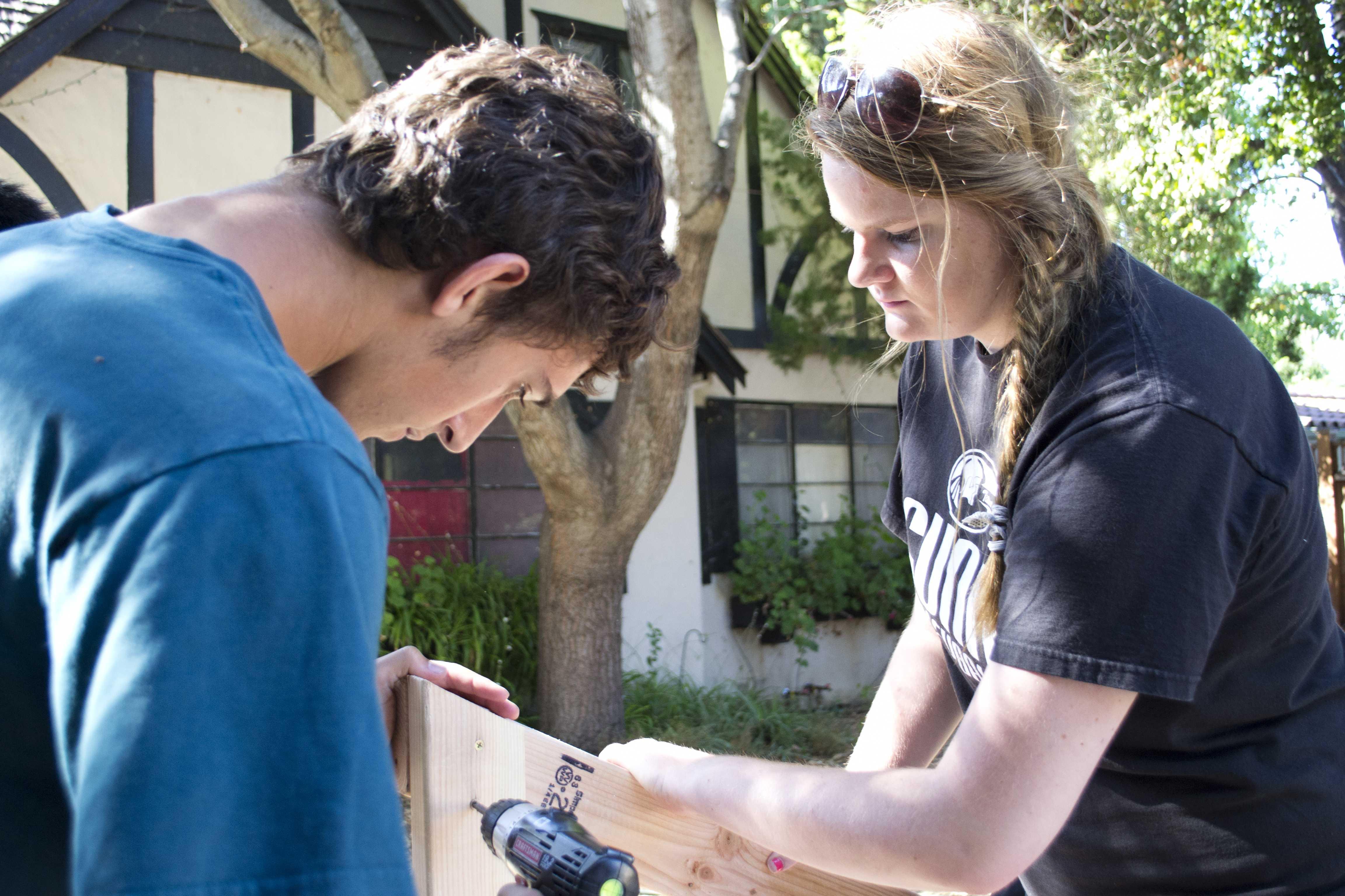Senior David Stelzer holds wooden planks while senior Schuyler Sun drills them together.