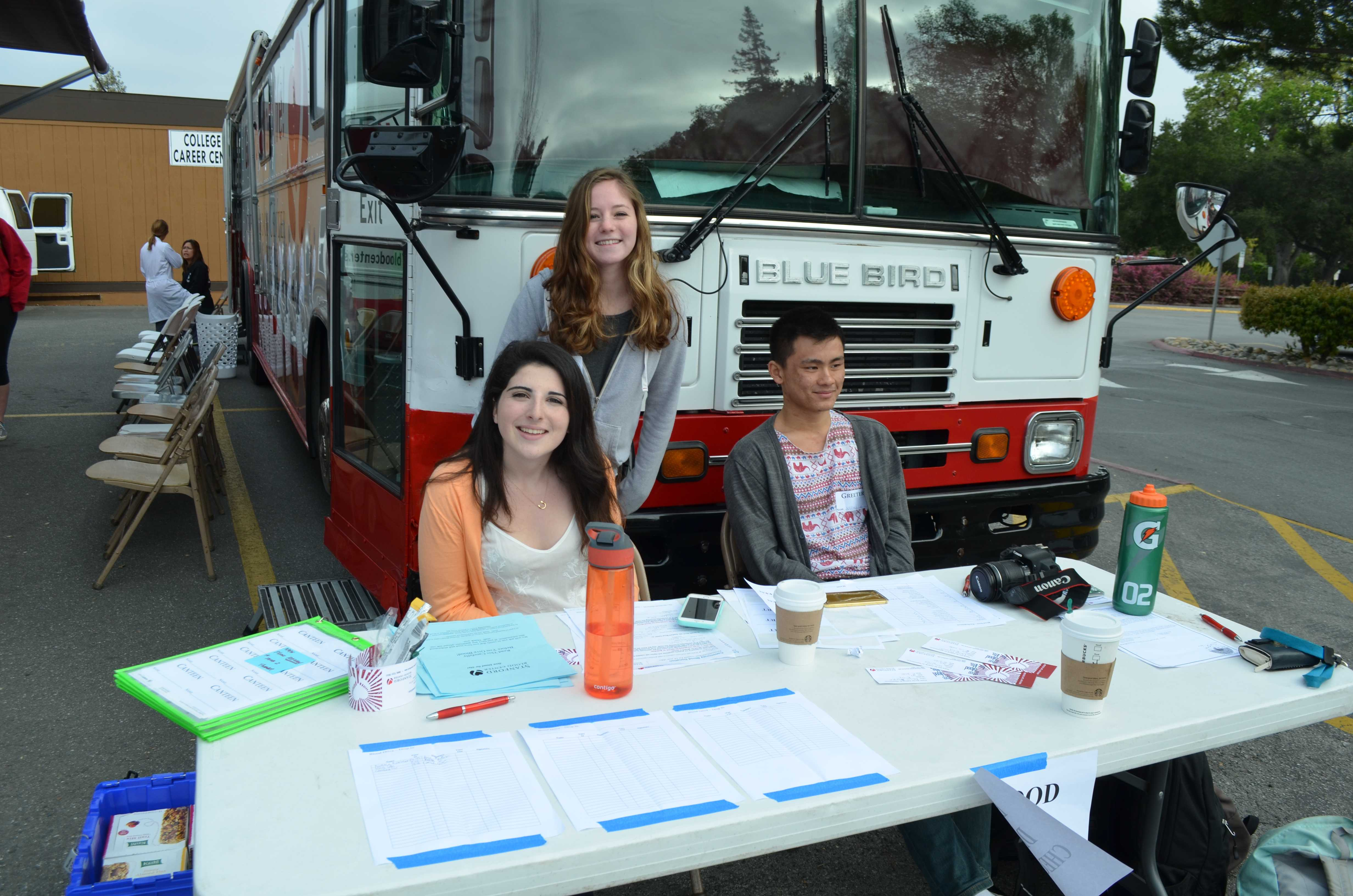 (From left to right): Junior Sarah Reich, senior Adi Steinhart and senior Jefferey Lee man the donor sign-up stand for Stanford Blood Center's blood drive at Gunn.