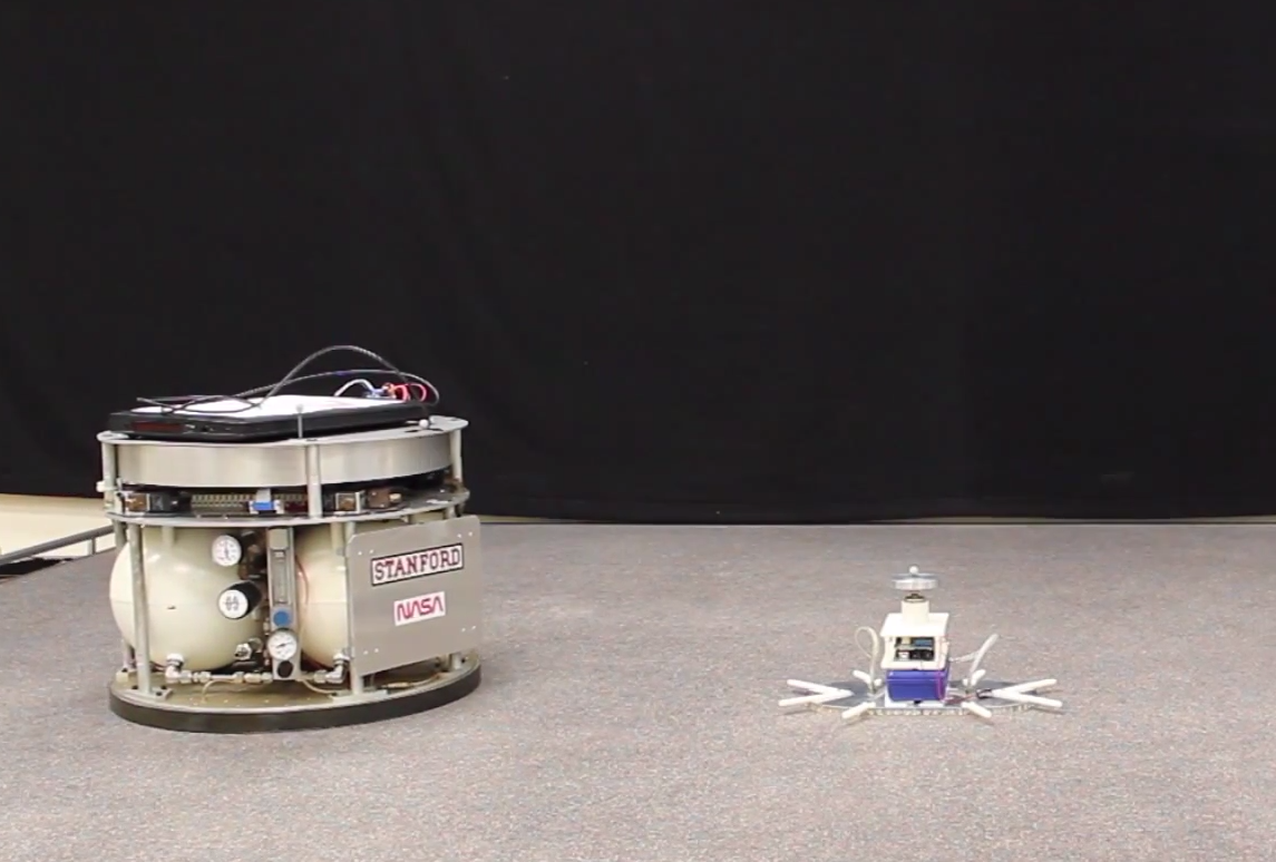 ree-flying spacecraft in motion (right), powered by compressed air with eight gas thrusters and a momentum wheel, about to maneuver around space obstructions.