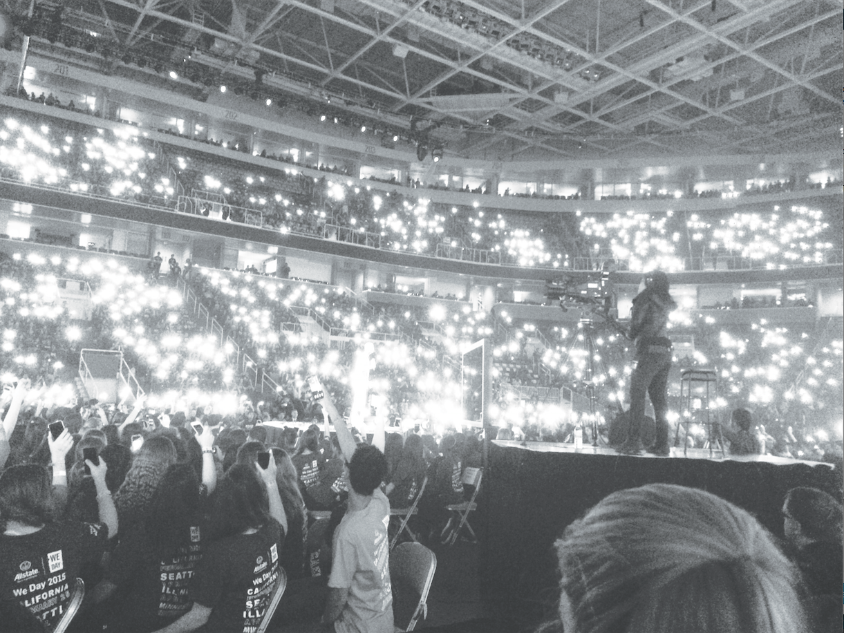 Students hold up their phones in the San Jose SAP center as lights to represent students' commitment to community service.