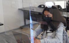 Freshman Lise Desveaux attends classes behind plexiglas.