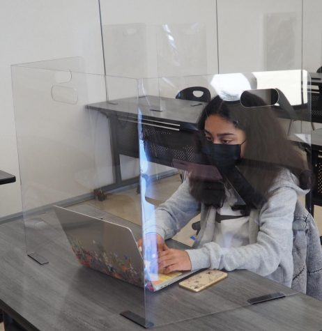 Freshman Lise Desveaux attends classes behind plexiglas.